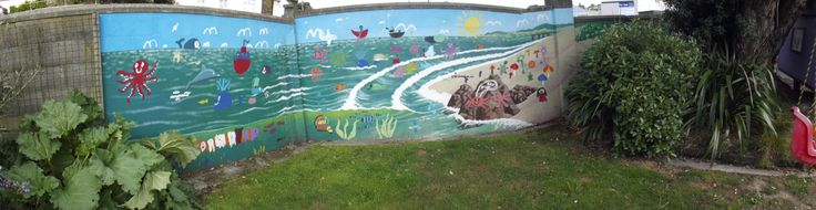 """Backyard Beach"", beach and ocean scene painted by Ellen populated by child painted elements. Aprox. 12msq, on corner of concrete wall. Private commission, Wellington"