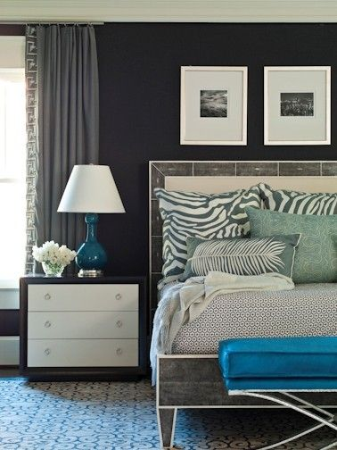 High contrast patterns in neutral colors, dark walls and accents of vibrant blue take this bedroom from quiet to dynamic!