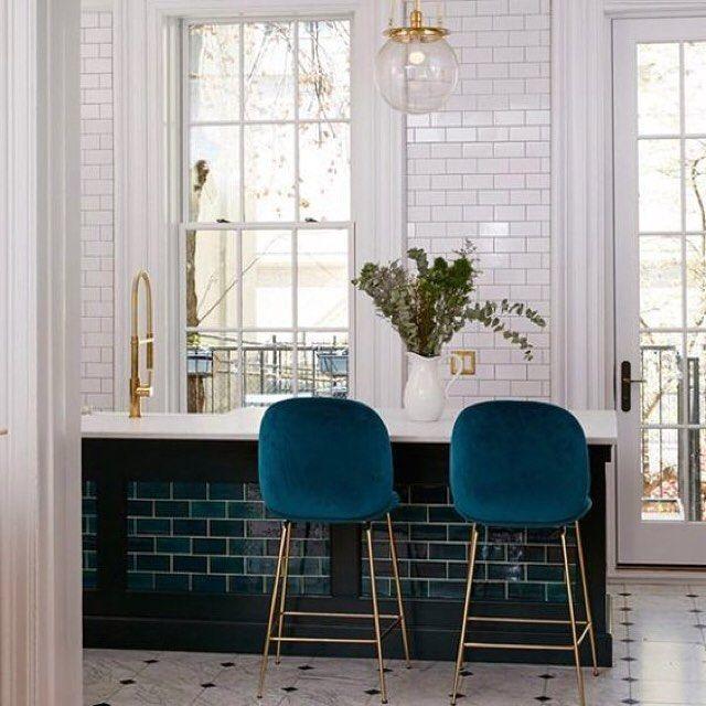 Dark tiles on bar and blue velvet and brass stools