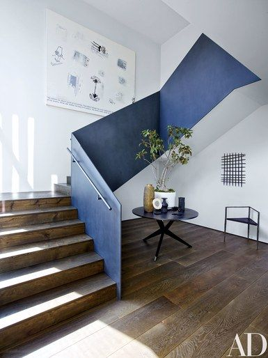 A Richard Prince painting hangs in the main stairway, overlooking a Hans Bellmann table, a Rick Owens chair, and a 17th-century Spanish iron grille | archdigest.com