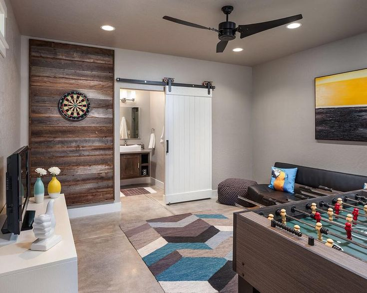 A modern pool house renovation in Eugene OR by #PorchPro @jordaniversonsignaturehomes. Check out that barn door and reclaimed wood dart board wall! (Link in bio)