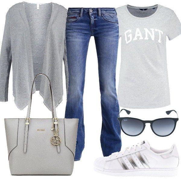 Un outfit per tutti i giorni composto da jeans bootcut, t-shirt con stampa, cardigan a righe e borsa a mano. Completano il look le sneakers Adidas Superstar e gli occhiali da sole Ray-Ban.