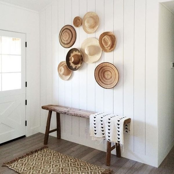 Beautiful neutral entryway with an unfinished wood bench, vertical shiplap walls and straw hats and woven baskets on display.