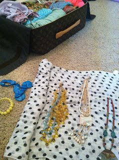 Packing necklaces by lining them up on a scarf, rolling it and folding it in half, then packing the little bundle into a structured suitcase.