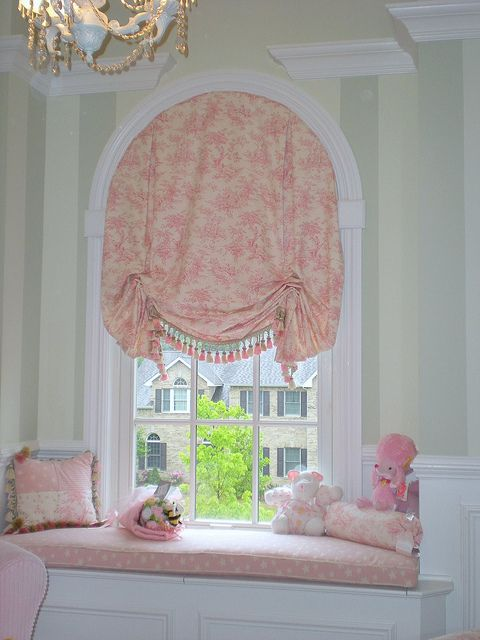 Pleated Balloon Shade On Arched Window Over A Window Seat.