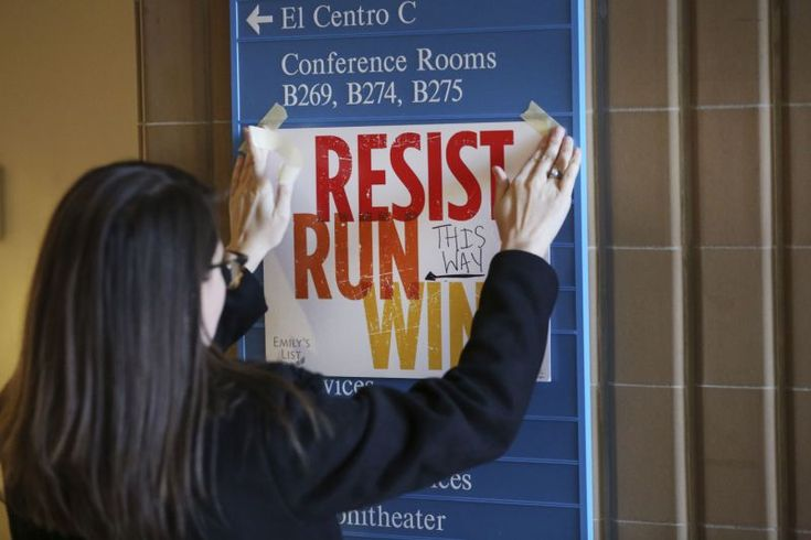 In this Saturday, Dec. 9, 2017 photo, Lianna Stroster posts a sign directing to a women's candidate training workshop at El Centro College in Dallas. EMILY'S List, an organization dedicated to electing candidates at all levels of government who support abortion rights, is conducting a national recruitment effort looking to train candidates and potential candidates in over 20 states. (AP Photo/LM Otero)