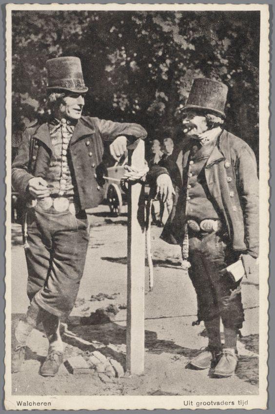 Twee mannen in Walcherse streekdracht. Op hun hoofd dragen de mannen een 'tunhoed'. Ze dragen een kuitbroek, middenvoor gesloten door zilveren 'broekstukken', terwijl de klep van de broek wordt gesloten door zilveren 'klapstukken'. Op het rechterdijbeen hangt de ketting van het horloge. De linker man draagt onder zijn jas een gedessineerde hemdrok, gesloten door een rij zilveren knopen. voor 1934 #Zeeland #Walcheren: