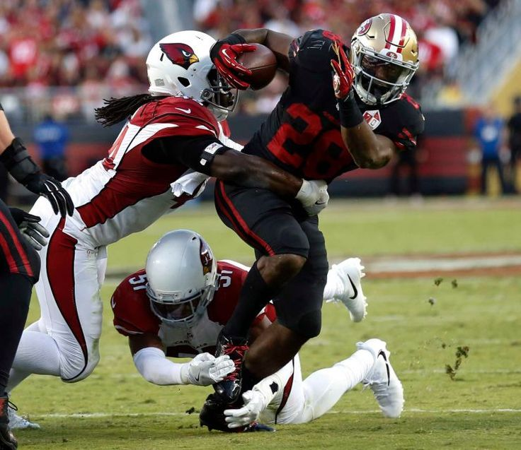 Thursday Night Football: Cardinals vs. 49ers  -  October 6, 2016:  33 - 21, Cardinals  -     San Francisco 49ers running back Carlos Hyde tries to break a tackle by Arizona Cardinals outside linebacker Markus Golden and middle linebacker Kevin Minter during the first half of their NFL game at Levi's Stadium in Santa Clara, California on Oct. 6, 2016.