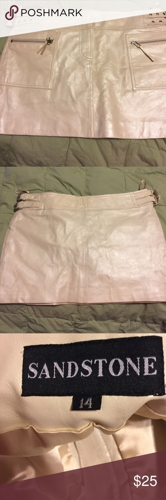 Pearl white leather mini skirt size 14 adjustable Cute mini with front pockets and side buckles on each side to tighten waist it is a size 14 real leather pearl like creamy white color! Small dot on right front by bottom of front right pocket, in last picture never worn! In excellent shape besides dot low price! Thanks for looking at my items! sandstone Skirts Mini