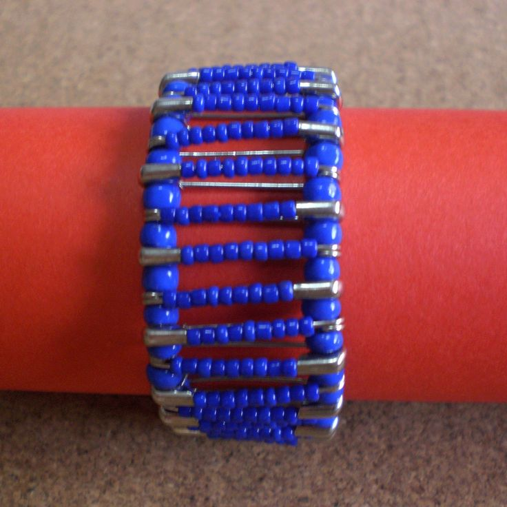 Bracelet made using safety pins with blue  plastic beads. Connected with large blue plastic beads.