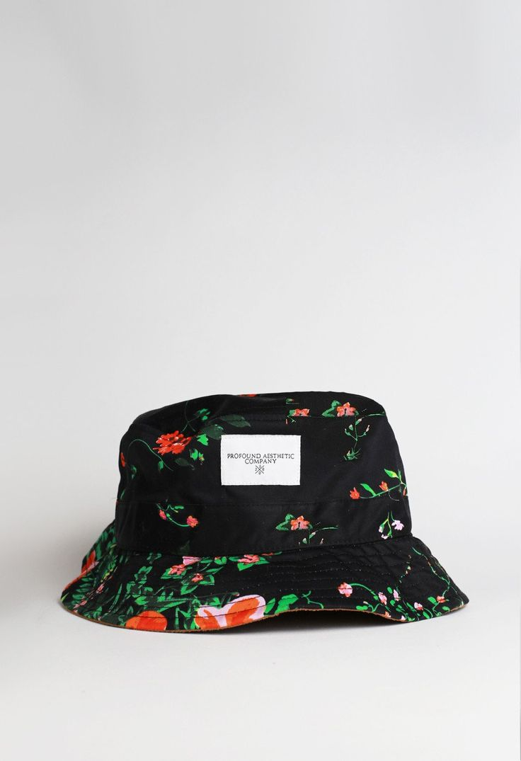 The Black Garden Floral Bucket Hat is composed of a black cotton construction that features an all over floral print.The floral arrangement showcases various vibrant colors including red, pink and green.The front of the bucket hat features a white cotton logo patch.The Black Garden Floral Bucket Hat is finished with a unique brown suede under-brim.