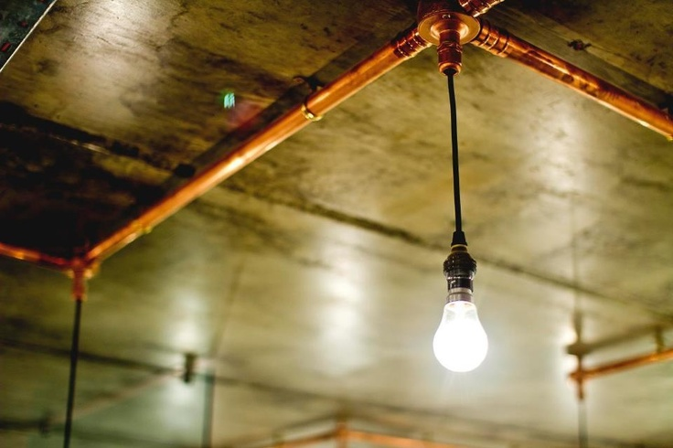 Naked Bulbs Suspended From Copper Piping Against Raw Concrete Ceiling Www