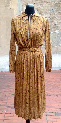 Original 1970s dress with abstract texture on warm colors, with a waist belt and particularly small velvet bow at the neck.