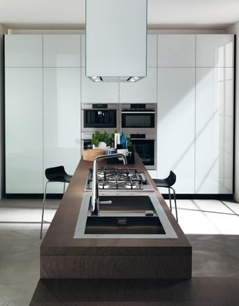 LiberaMente by #Scavolini. Counters fitted with hobs, sinks and integrated tables can outlines spaces by giving them a strong character, as this composition  with a continuous development shows (#kitchen and #living room in the same room), which also features latest generation electrical appliances (squared Laguna hood and multifunction ovens).