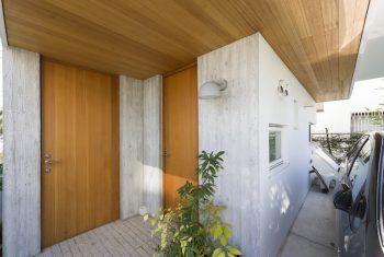 外観の印象を優しく豊かにしてくれる木製の玄関ドア。手前が自宅、奥がゲストルームに続く。