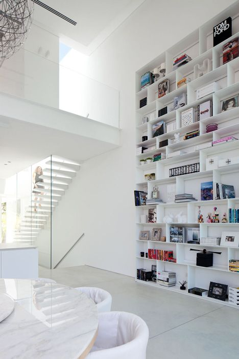 Tiny house design idea: all white decor makes a smaller space feel airy and big, one wall of floor to ceiling shelves provides a visually striking storage solution (so much color in a sea of white). Barak House by Pitsou Kedem.