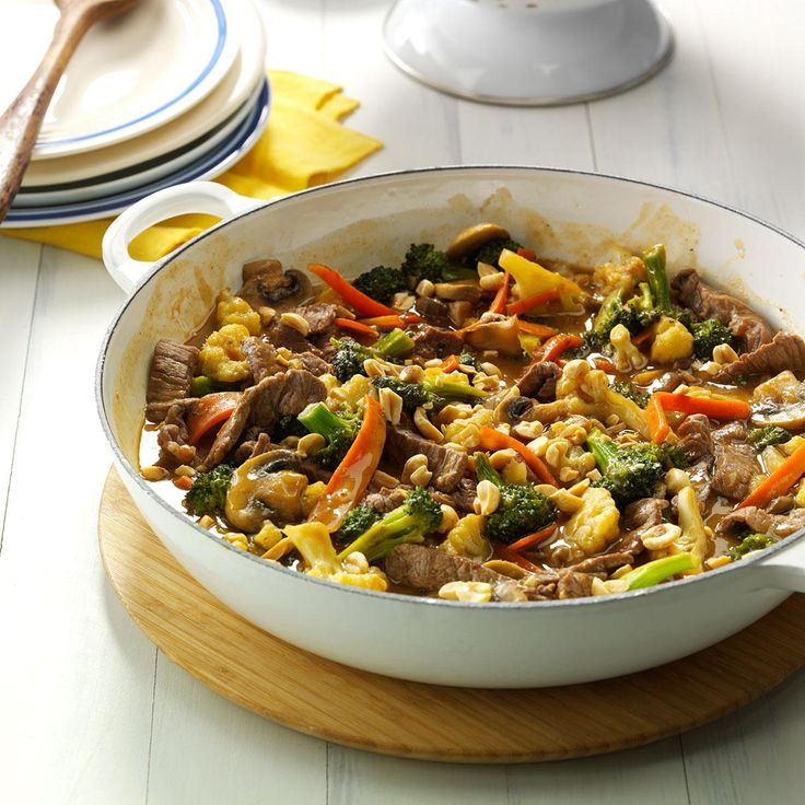 Thai Beef Stir-Fry Recipe -A distinctive peanut sauce complements this colorful combination of tender sirloin strips, cauliflower, carrots, broccoli and mushrooms. I like to dish it up over spaghetti, but you could also use fried noodles.—Janice Fehr, Austin, Manitoba