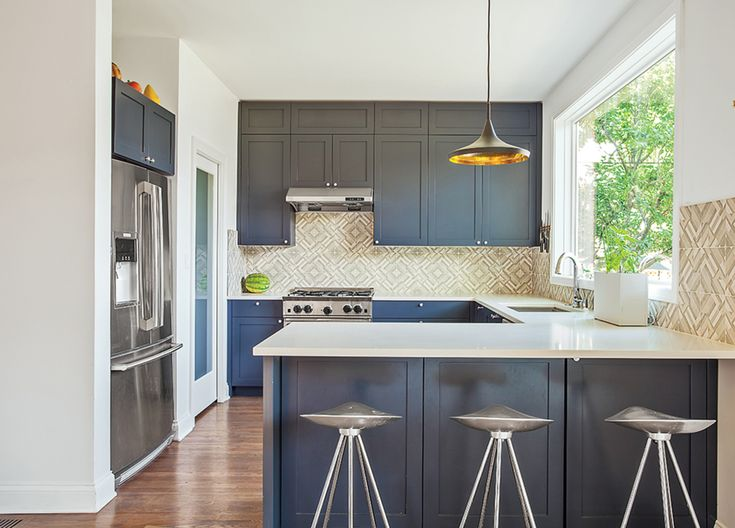The kitchen sports blue-gray cabinets and Azulej tiles by Patricia Urquiola for Mutina. The Currys keep an eye on the backyard through a large Pella window, situated above a sink with a Sensate faucet from Kohler. The range is by BlueStar.