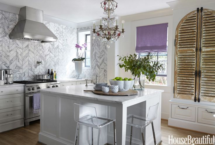 In a Birmingham apartment, an entire wall is clad in Calacatta Gold marble tiles from Kenny & Company and laid in a chevron pattern for extra drama. Click through for more kitchen backsplash ideas.