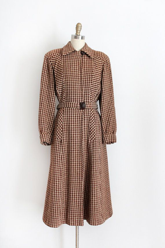 Absolutely stunning brown wool houndstooth coat from the very early 1940s. This coat features a flattering silhouette, gorgeous hand carved wood button and belt buckle, and shoulder pads.