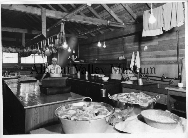 Cook Bob Larson, in the camp kitchen for the Logging Operations at Franklin River, near Port Alberni, BC, c1941.  Note the tubs of steaks in the foreground to feed hearty logger appetites.  Photographer: Leonard Frank.  [Alberni Valley Museum Photograph Collection, PN20090]