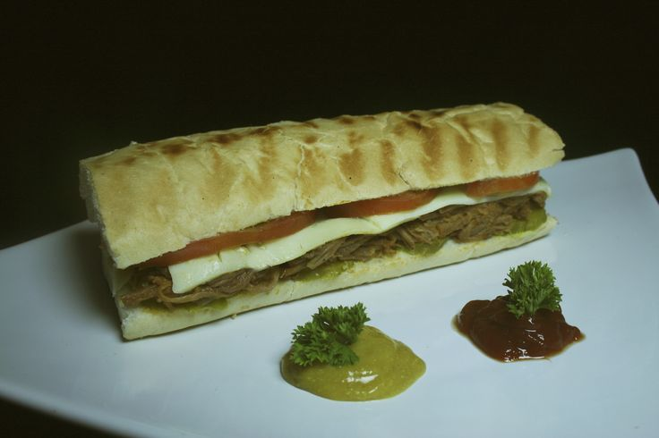 Sandwish ropa vieja: pan artellano, tomate, queso, carne deshilachada.