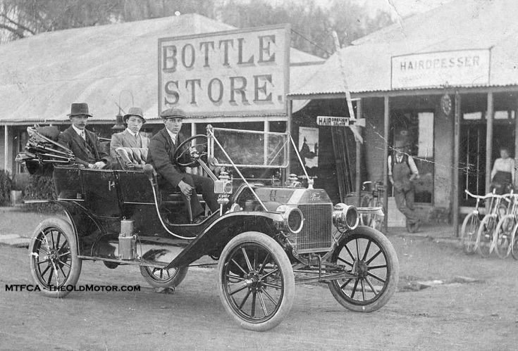 """1911, Canadian manufactured, r.h.d. Model """"T"""" Ford driving past the Bottle Store (a liquor outlet?), which was next door to a hairdresser that the women must have ridden their bicycles to and from in the pursuit of beauty."""