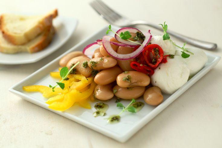 Pulite ed affettate il peperone a striscioline. Disponete nei piatti e coprite con i fagioli scolati. Guarnite con la mozzarella e decorate con i pomodori secchi tagliuzzati e la cipolla a fettine. In