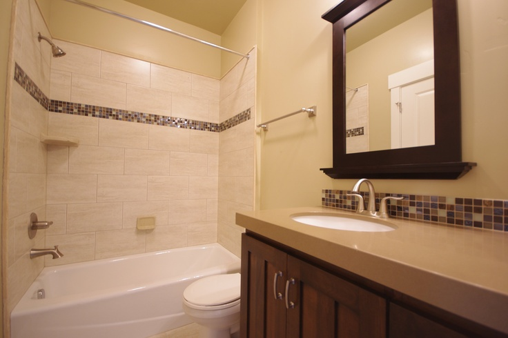 Simple glass liner is a great way to add detail to a plain tub surround.     #GlassMosaic #Tile #Shower #Bathroom