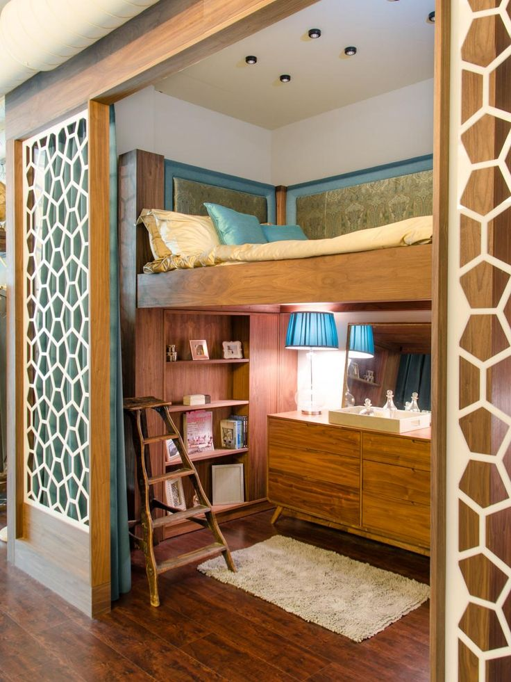This bedroom alcove was created with a custom raised bed and upholstered headboard, enabling a dressing and storage space to be housed beneath. Geometric panels akin to a giraffe's hide create a cool safari vibe in this midcentury loft.