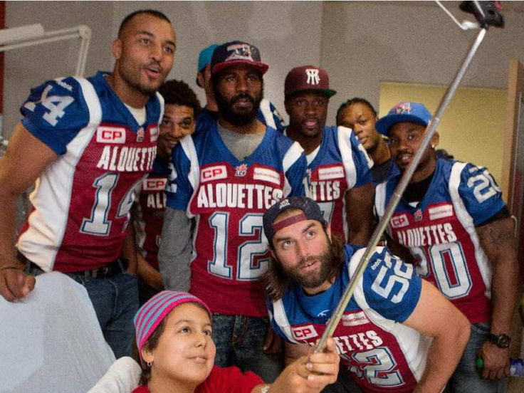 Sara Gibeau uses a selfie stick to get a picture with the Montreal Alouettes as they visit Ste-Justine Hospital in Montreal on Tuesday October 6, 2015.