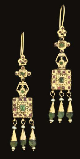 A PAIR OF MOROCCAN EMERALD INSET GOLD EARRINGS   FEZ, FIRST HALF 19TH CENTURY   Each with a square panel with central rectangular emerald flanked by smaller similar red stones, three pendant emerald drops below, the reverse plain, suspended on a hoop below an emerald and garnet inset cruciform panel, on gold hoop
