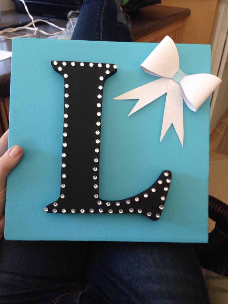 Diy dorm canvas initial. Bought a square blank canvas, wooden letter and scrapbook paper. Used the bow idea from another pin using paper(diy bow garland), painted the canvas, painted the letter and applied stick on gems. The hot glued initial and bow to canvas!:)