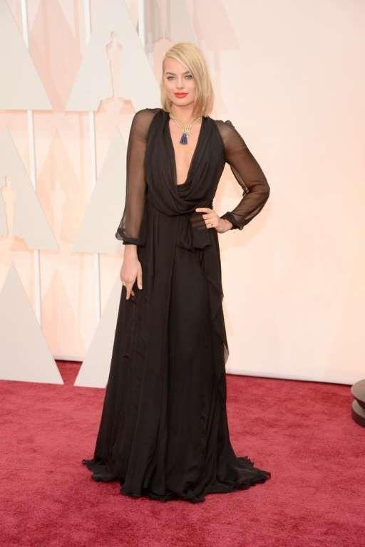 Margot Robbie Un vestido negro cruzado hasta los pies con mangas translúcidas de Saint Laurent fue el elegido por Margot Robbie para la gala.