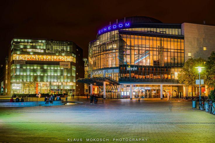 https://flic.kr/p/AppcZr   Köln cinedom - Mediapark  -  cologne   Der Cinedom ist ein Multiplex-Kino im Mediapark in der Kölner Innenstadt, das im Dezember 1991 dort mit großer Medienpräsenz als erstes Gebäude eröffnet wurde. Es ist das nach Anzahl der Plätze fünftgrößte deutsche Multiplex-Kino.[1] Es beherbergt 3748 Sitzplätze in 14 Sälen, die jeweils mit bis zu 40 Lautsprechern ausgestattet sind.[2] Unter anderem haben dort Tom Cruise, Harrison Ford, Britney Spears, Angelina Jolie…