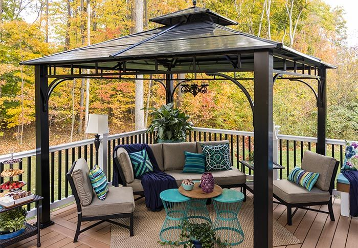 A Gazebo on a Composite Deck with Patio Chairs, a Couch and an Outdoor Rug.