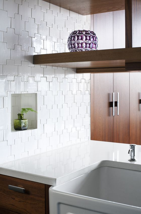Cross-shaped tiles, Ann Sacks Gotham Swiss Cross, create a lovely texture for the all-white backsplash — a nice departure from the common subway tile. Countertops are Caesarstone in Eggshell, with an under-mounted farmhouse sink by Whitehaus.