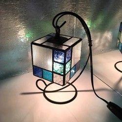 ステンドグラスの技法で制作したテーブルランプ。色んなブルーを散りばめた 見た目にも爽やかな雰囲気のランプです。11㎝の四方形で 寝室や玄関先など 場所を問わずに飾って頂けます。放射線状に広がる色影がとても美しい作品となっております(^_−)−☆手作りの木製配線台、電球込みの価格です。追跡 補償付き ヤマト運輸で発送致しますのでご安心下さい。サイズ 11㎝四方形ブルーハンドメイド2017シンプルハンドメイド2017特別企画1705