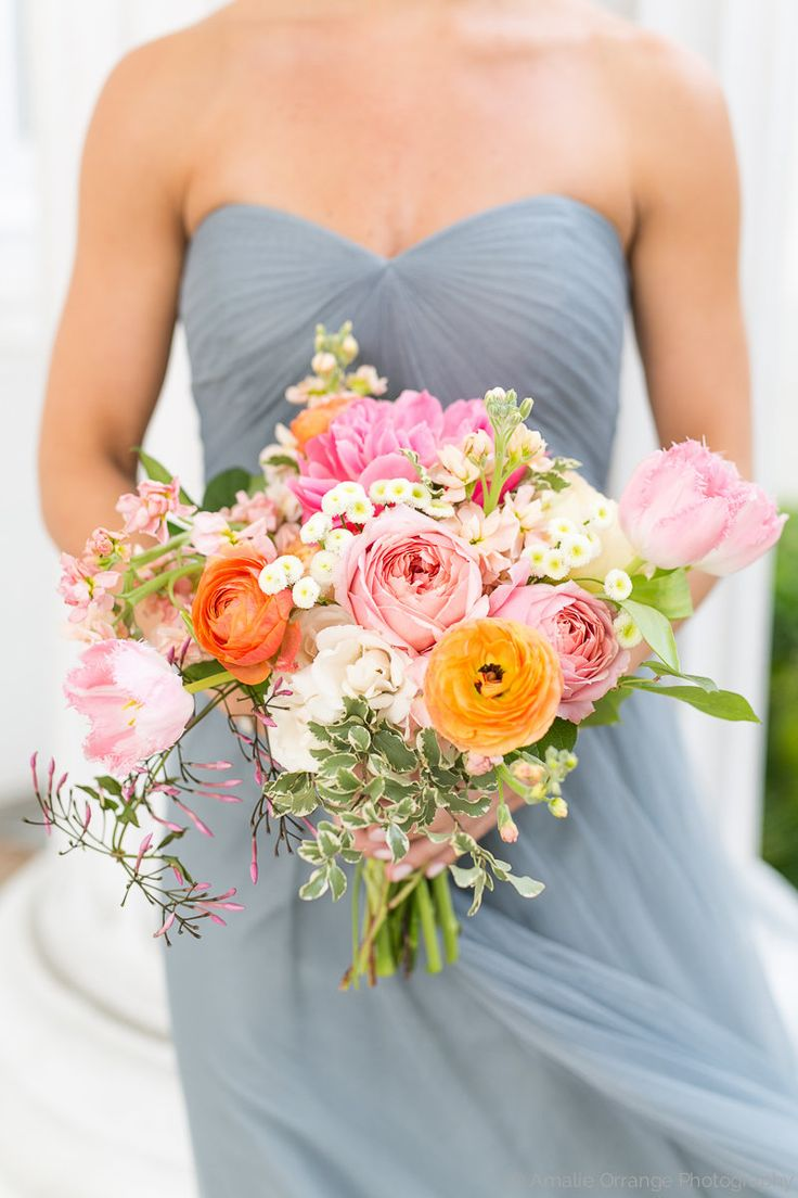 bridesmaid in a strapless slate gown holds a loose bouquet of spring flowers including coral charm peony, romantic antique garden rose, caramel antique garden rose, peach stock, pink fringe tulip, peach ranunculus, white majolik spray rose, white button chamomile, variegated italian pittosporum& jasmine vine wrapped in cream satin ribbon.