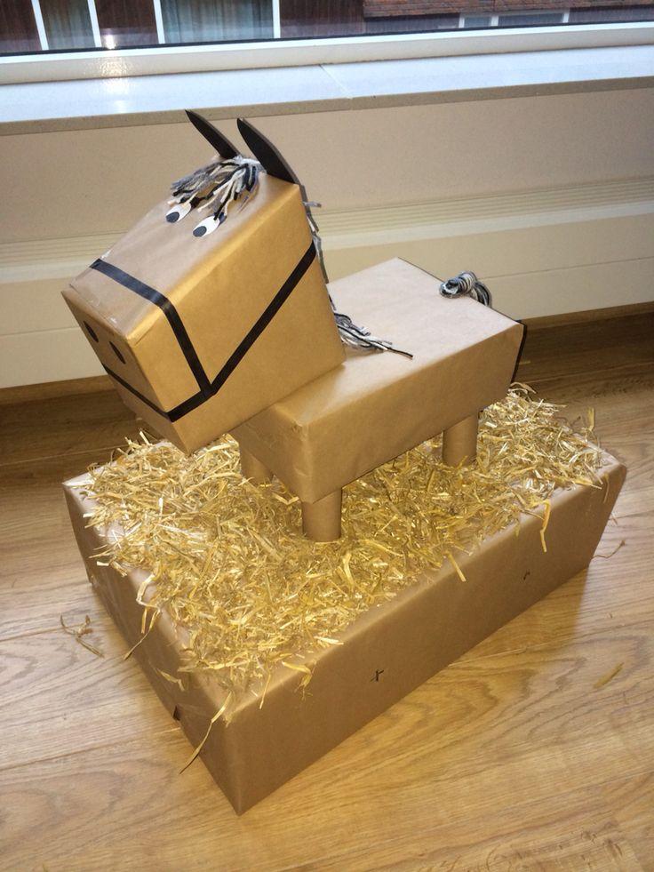 Sinterklaas surprise. Dit paard is gemaakt van dozen, bruin inpakpapier, wol, lijmpistool, zwarte stift, zwart papier en wat hooi/stro. Het cadeau zit in de doos eronder. Aan de zijkant zijn twee verborgen gaten gemaakt. Daar kun je met je armen in en grabbelen naar t cadeau. De cadeautjes hebben we verstopt op t 'plafond' van de doos en aan de zijkant,