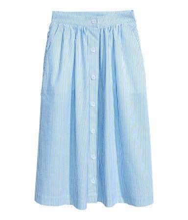 Light blue/white striped. Flared, knee-length skirt in striped seersucker with buttons at front and side pockets. Concealed, extended waistband tab with
