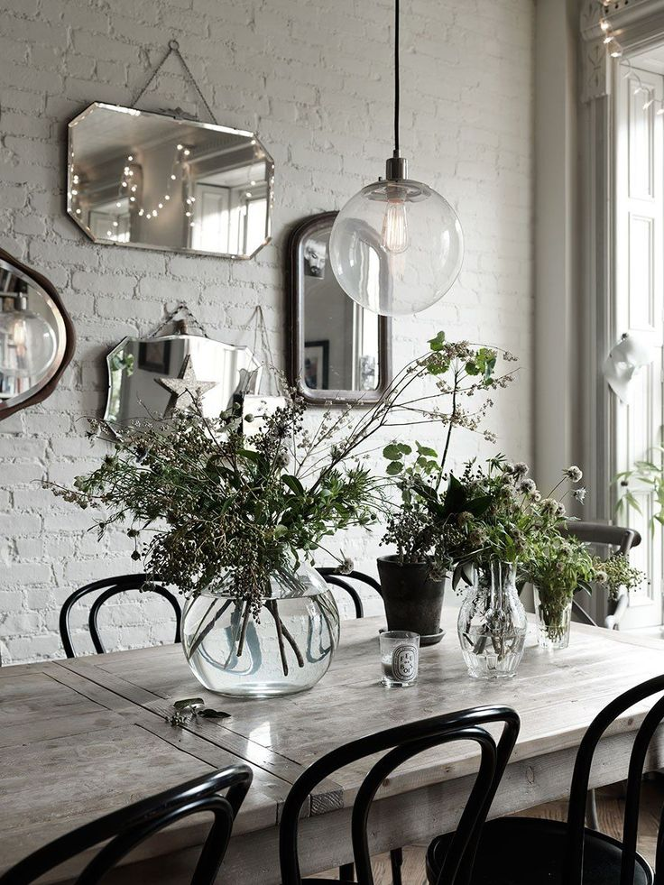 At home with Nina Persson with white washed walls and vintage mirrors as wall art . Fireplaces, ceilings and the bare brick walls surround lots of and flea market finds.