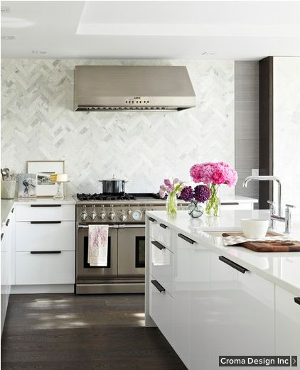 The showstopping herringbone marble backsplash is fashioned out of 2- by 8-inch Calacatta Michelangelo tiles.