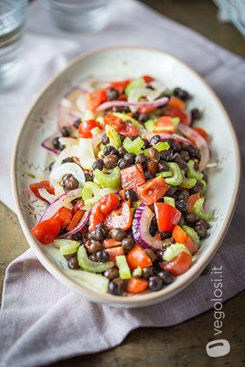 Insalata di ceci neri, sedano, pomodori e cipolle con olio alle erbe