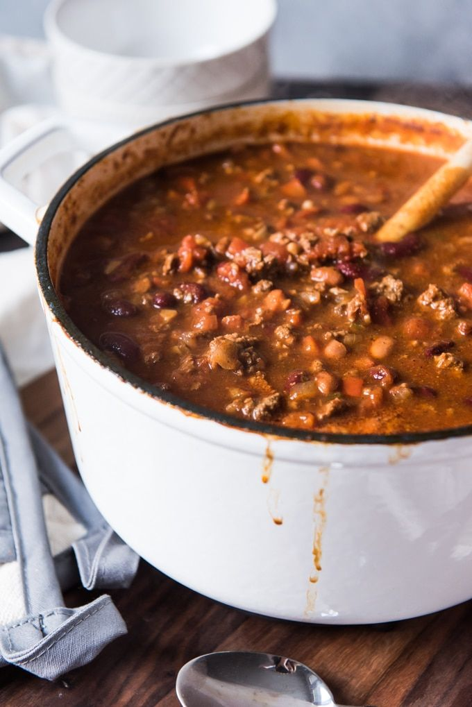 A Large White Dutch Oven Of Chili Loaded With Beans Browned Ground Beef And Mushrooms Along With Tomatoes And Spices Mushroom Chili Food Oven Chili Recipe