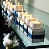 Create your own Hanukkah menorah with glass tea-light holders set on wrapped boxes. Secure candleholders with double-sided tape.