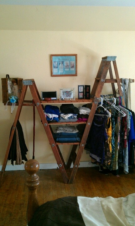Reclaimed wood and ladders stained and used as a closet.