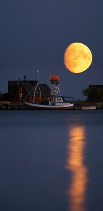 Fishing village and full moon with calm sea in the foreground at Gotland, Sweden