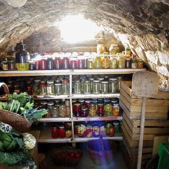 Wnętrze ziemianki najlepiej umeblować prostymi półkami, na których poustawiamy skrzynki, kosze z warzywami, kolorowe słoje z konfiturami, no i butelki wina.