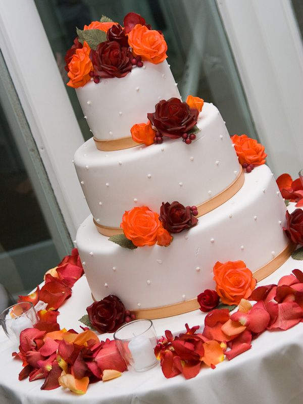 A cake done in striking autumn colors. Do the design with a ribbon around the base of each tier, sugar pearls for the sides, and silk or gum paste flowers. Gorgeous!